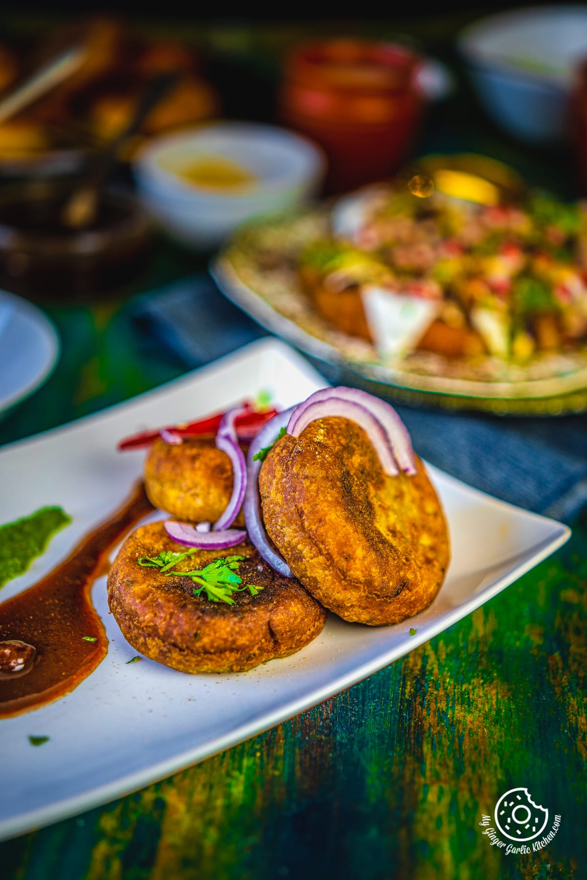 three aloo tikki served in a white plate with green coriander chutney and tamarind chutney