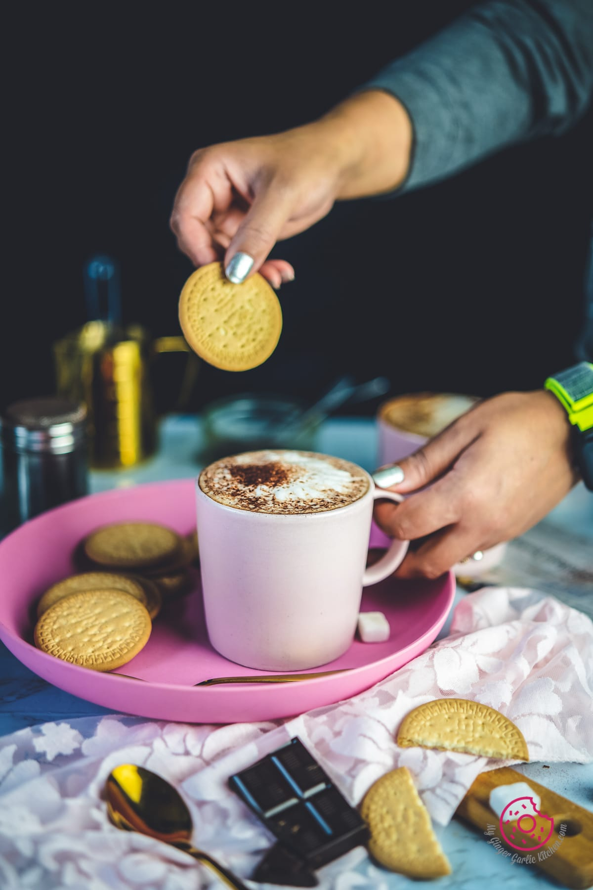 a woman holding biscuit over cafe mocha