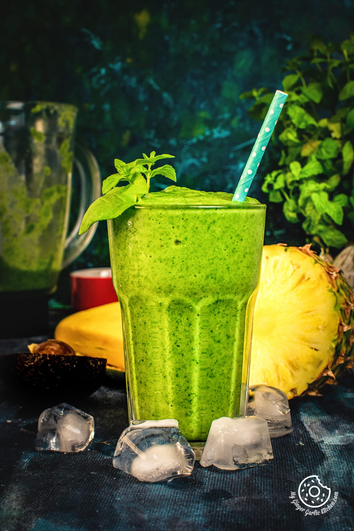 green smoothie in a tall glass and pineapple in background