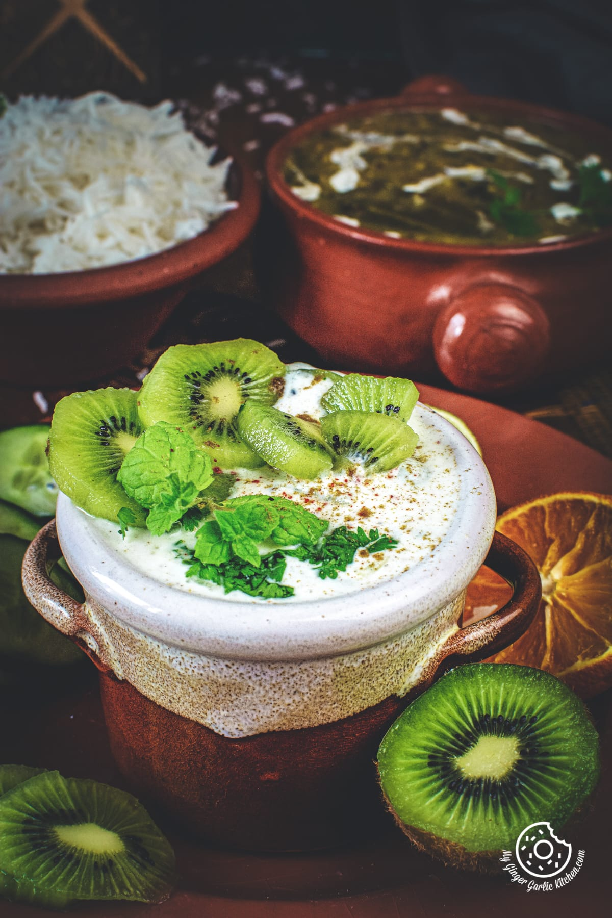 closeup shot of kiwi raita served in a brown and white dish
