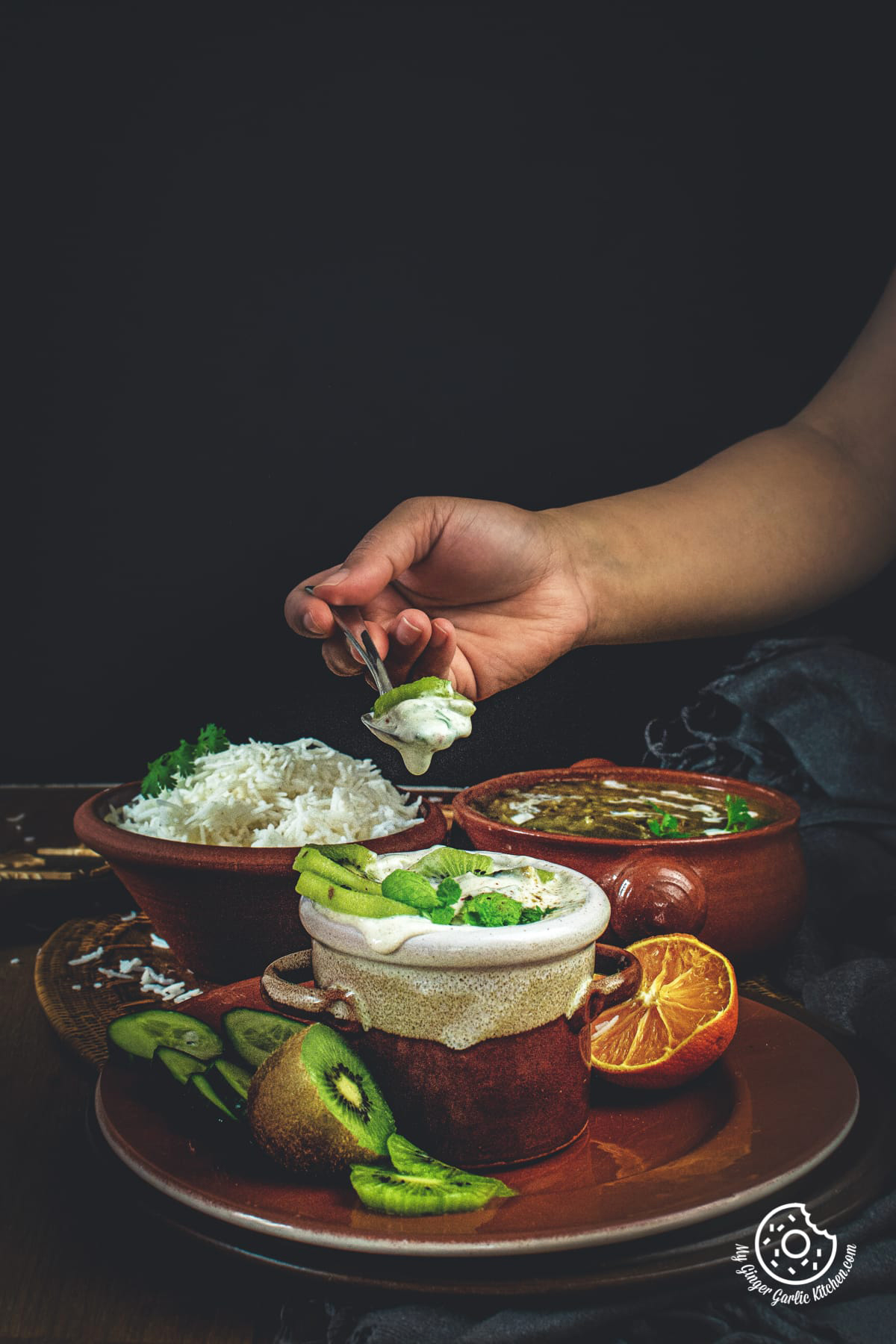 a woman holding a spoon over kiwi raita dish