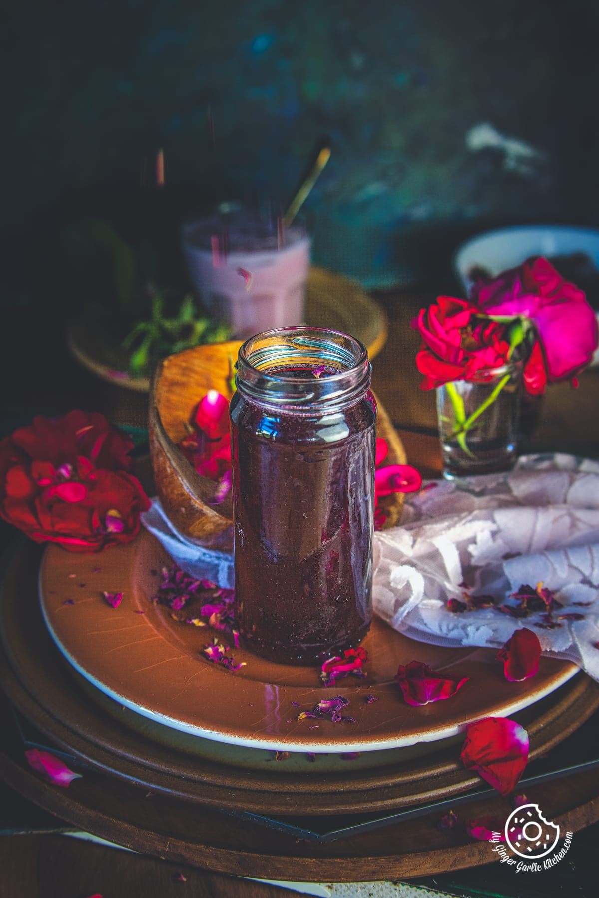 homemade rose syrup in glass bottle and fresh rose petals in background