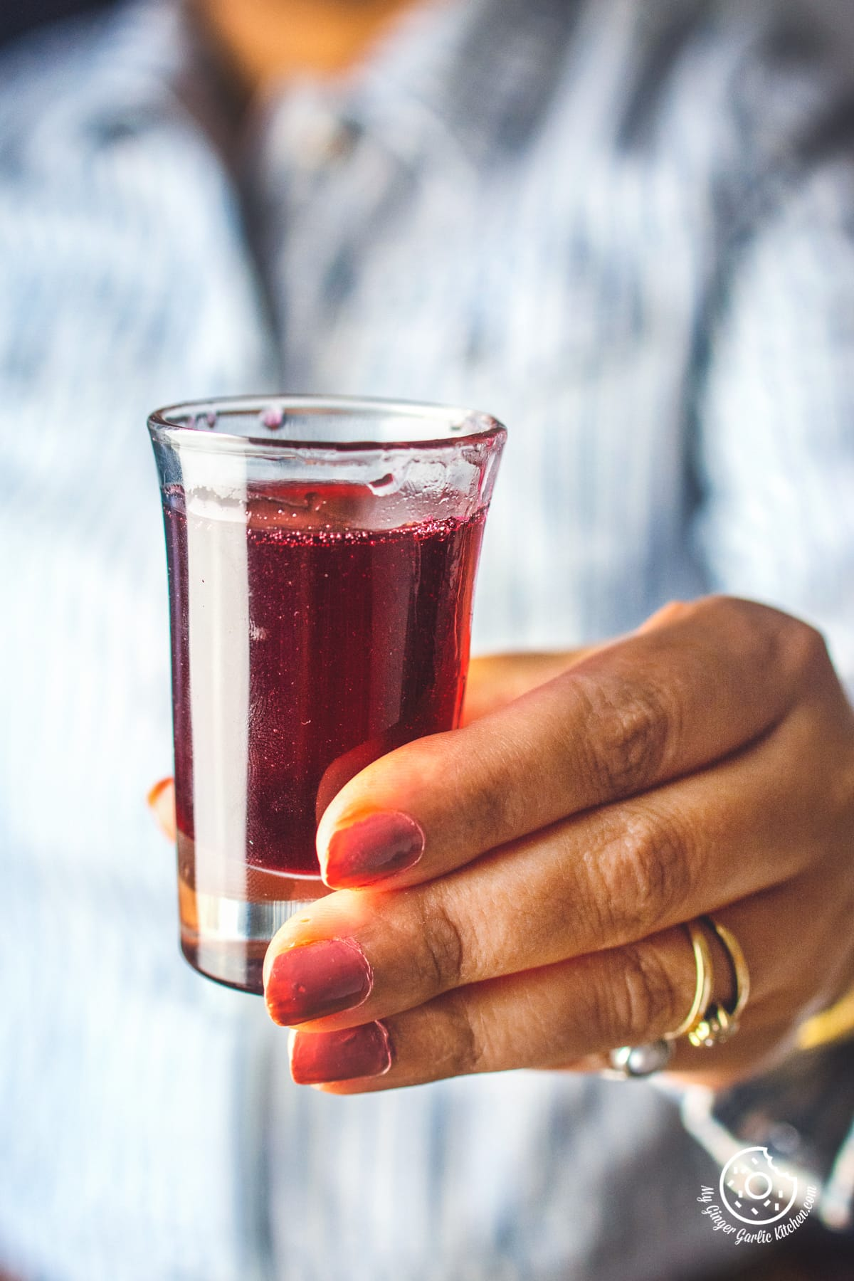 a female holding homemade rose syrup small glass