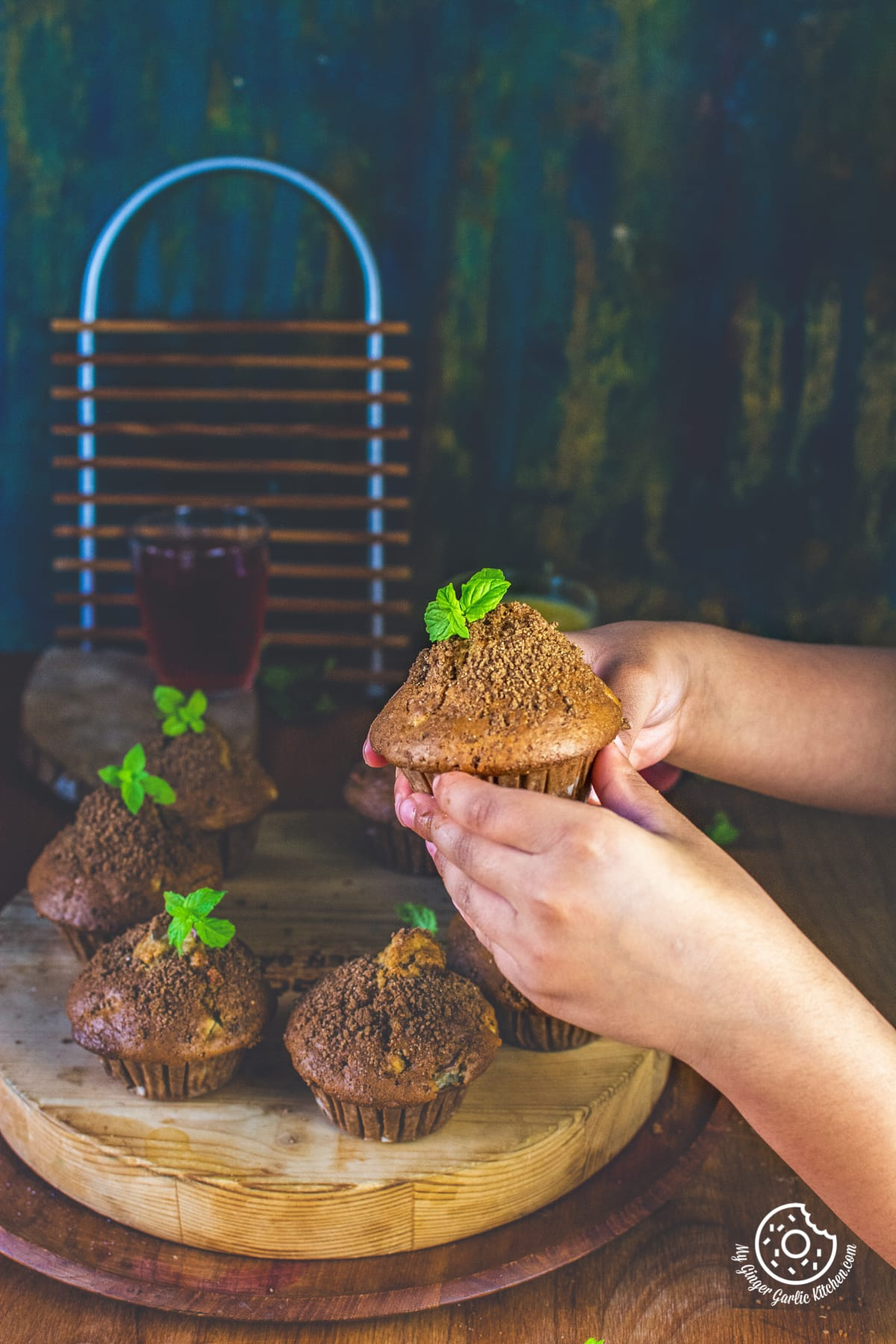 a kid holding whole wheat peach muffin topped with mint leaves