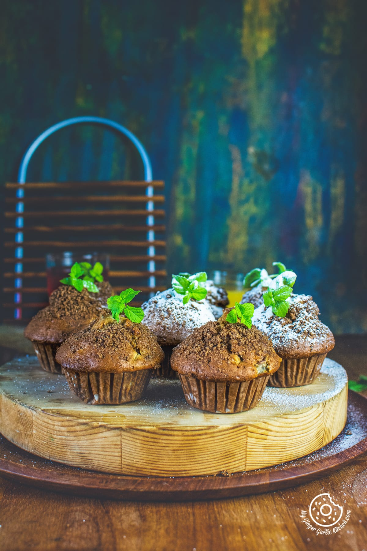 whole wheat peach muffins topped with mint leaves served on a wooden board