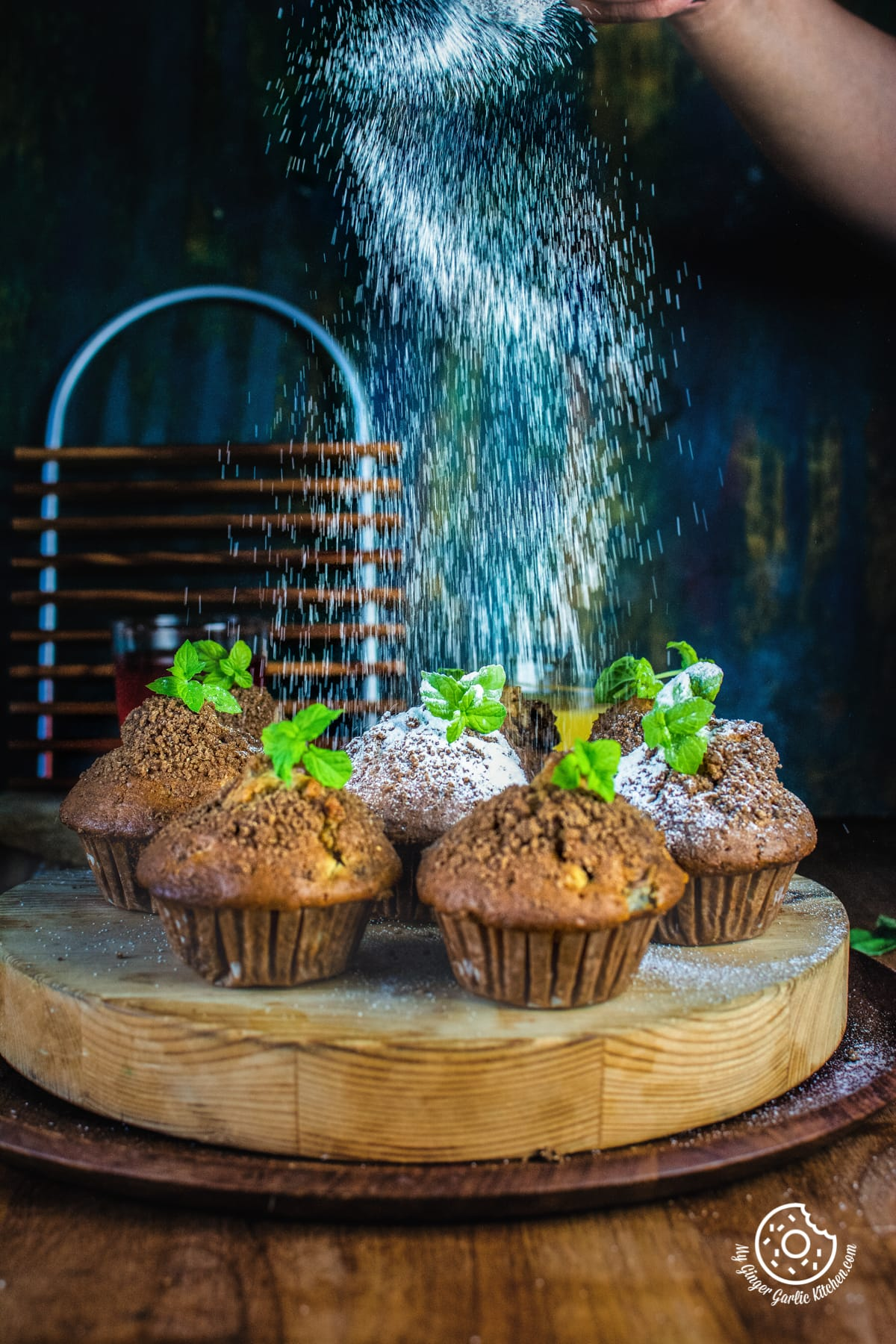 sugar sprinkling on whole wheat peach muffins topped with mint leaves