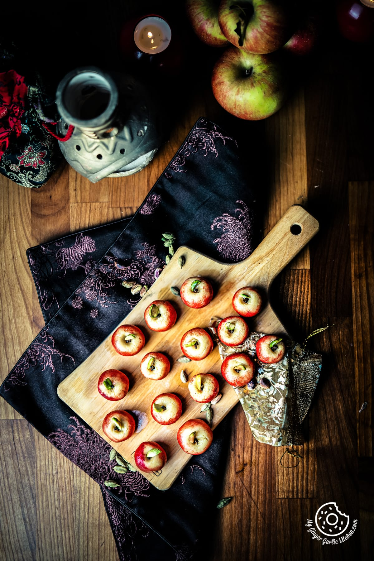 overhead shot of milk peda served on a wooden cutting board and apples on the side