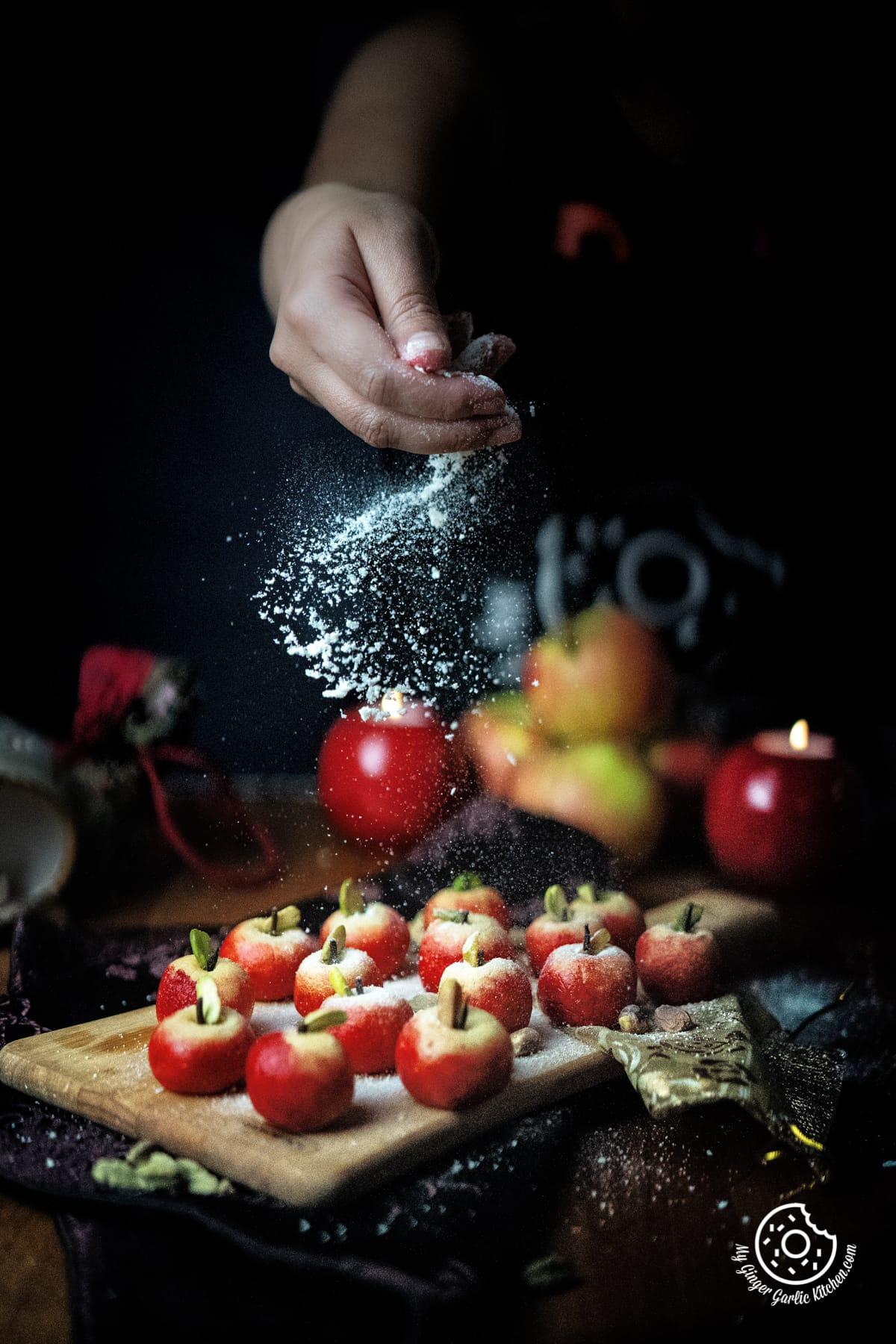 a female sprinkling milk powder over apple shaped milk peda