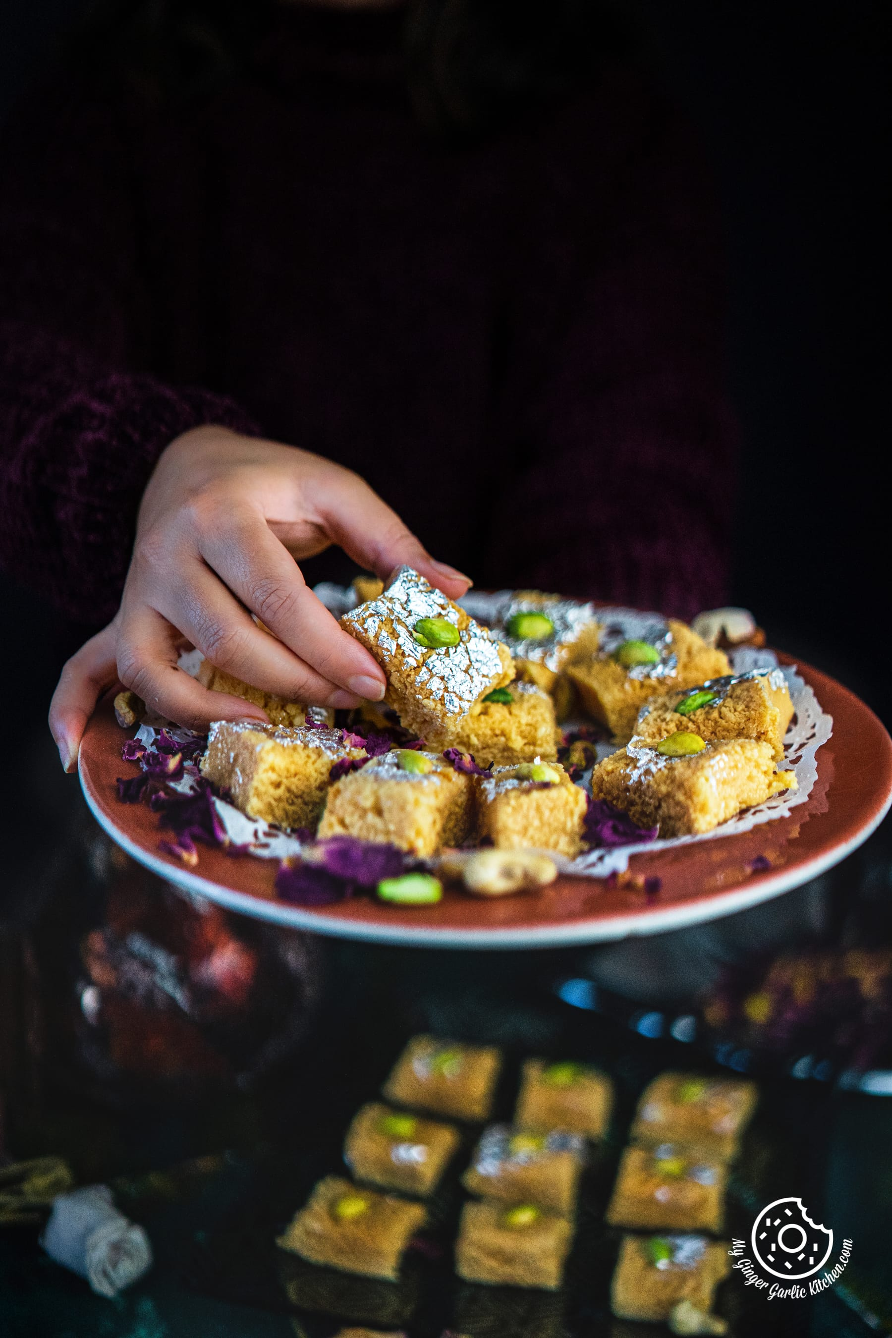 a hand holding indian milk cake or alwar ka mawa served in a brown plate