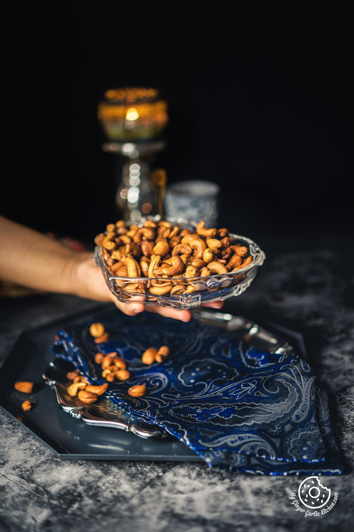 a hand holding masala kaju (spicy roasted cashew nuts) served in a heart shape transparent bowl