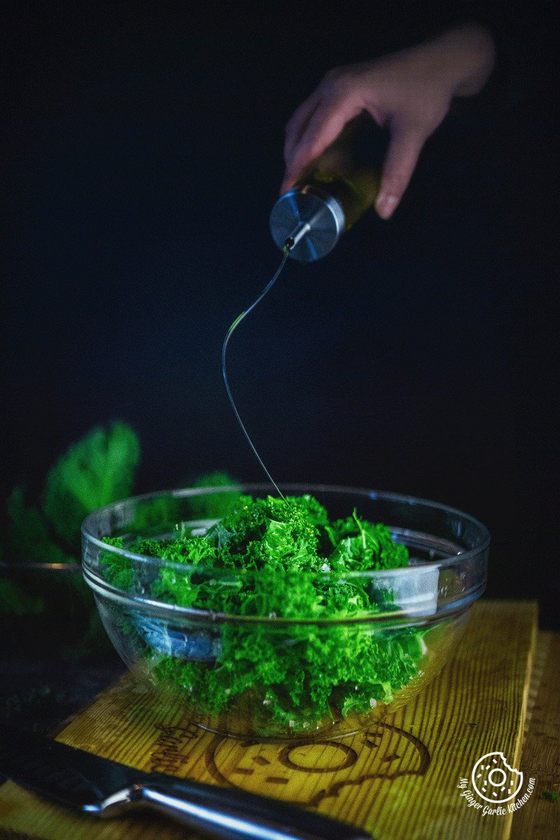 image of oil pouring over Kale leaves