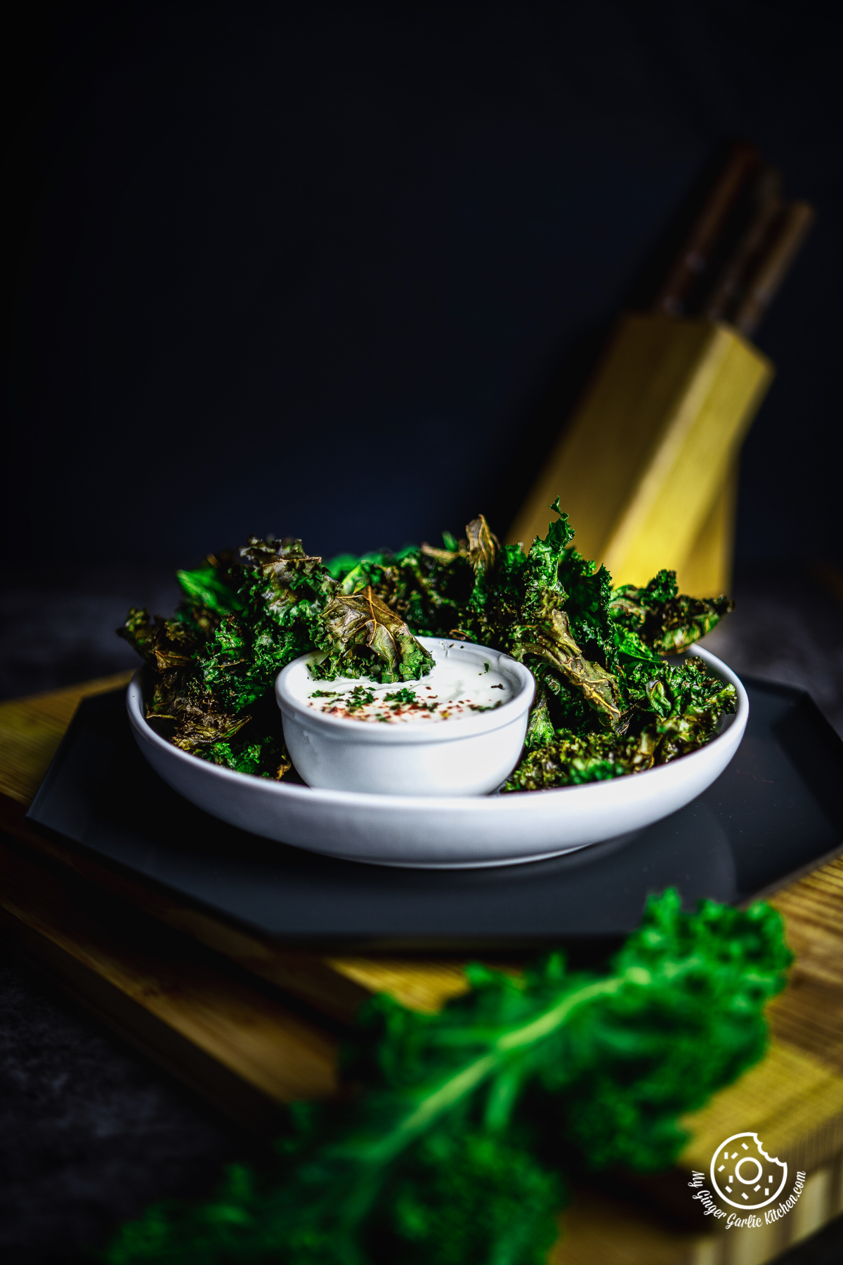 air fryer kale chips in a white plate with dip bowl