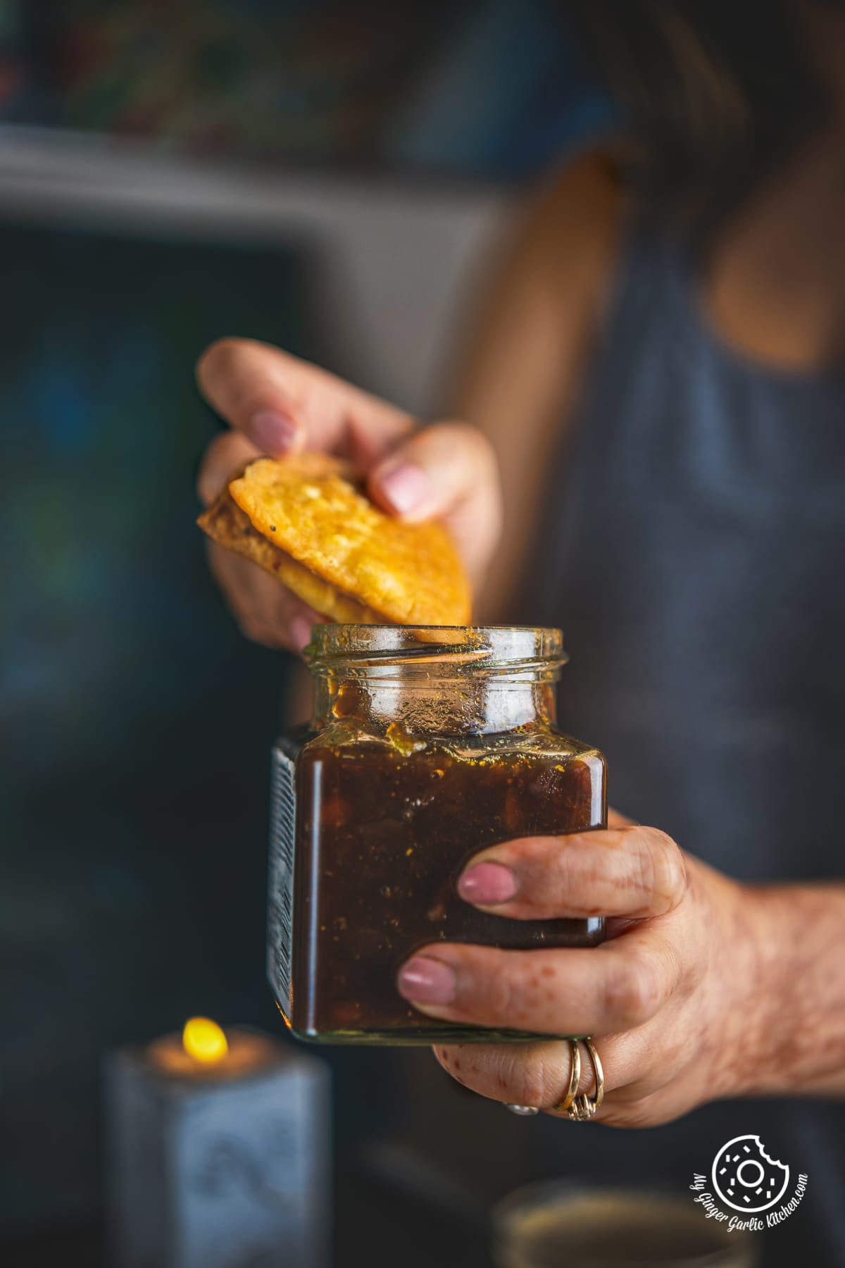 Image of a female holding Cheese Garlic Masala Mathri over a chutney jar
