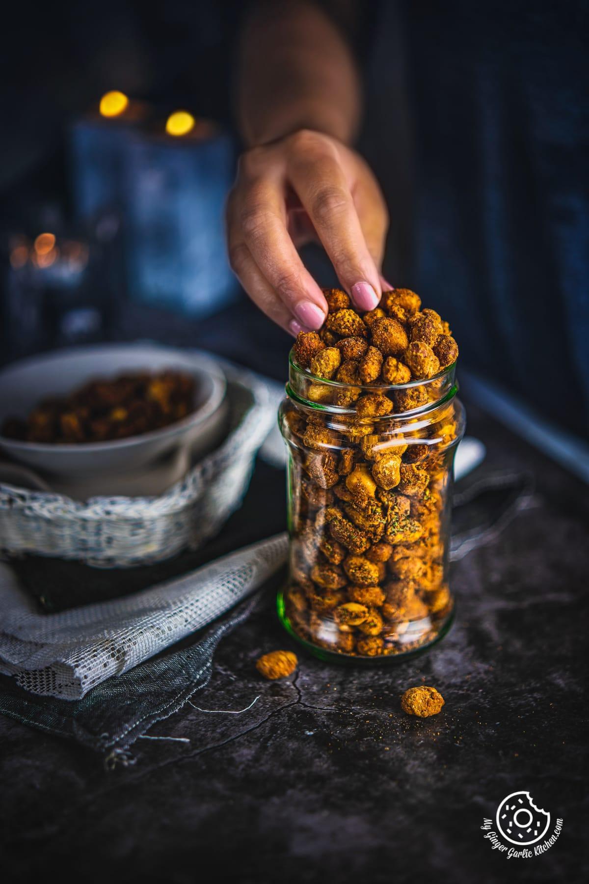 a hand picking masala peanut from a transparent jar