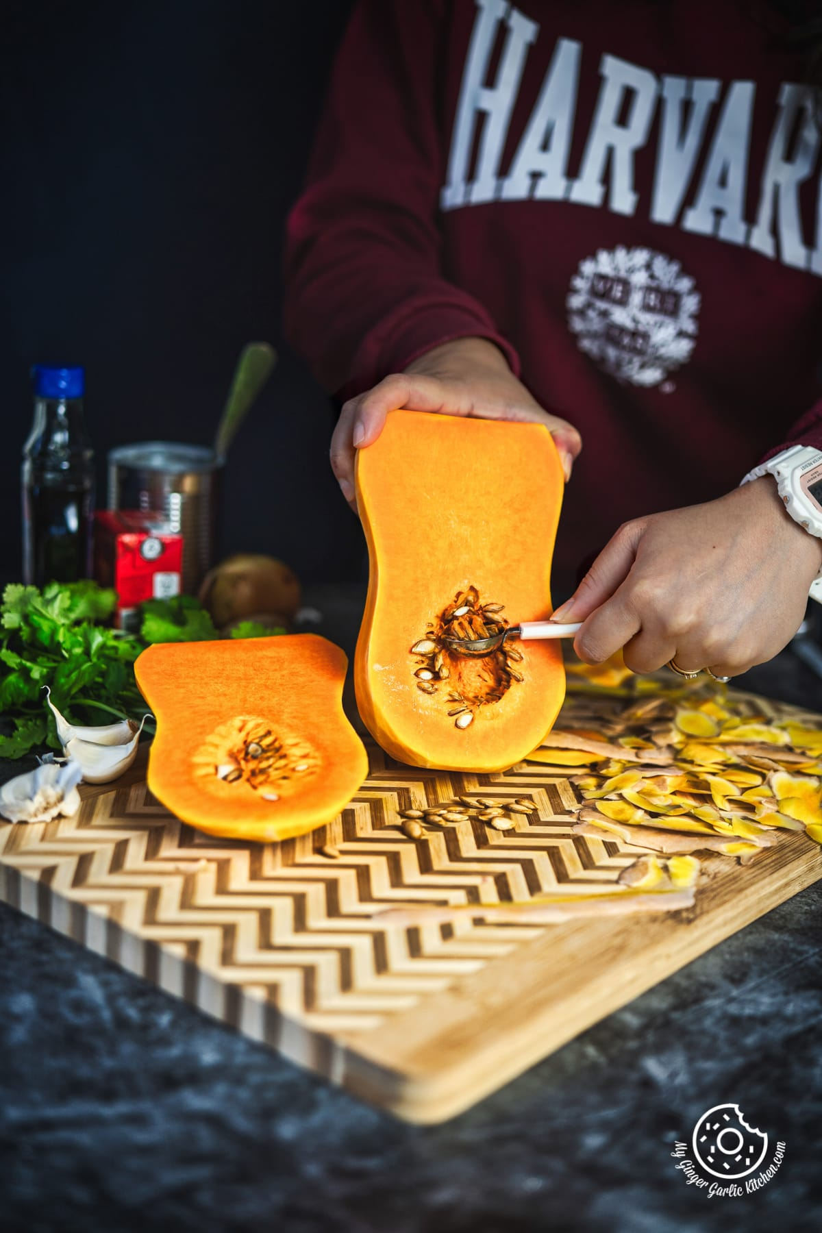 Person removing seeds from butternut squash