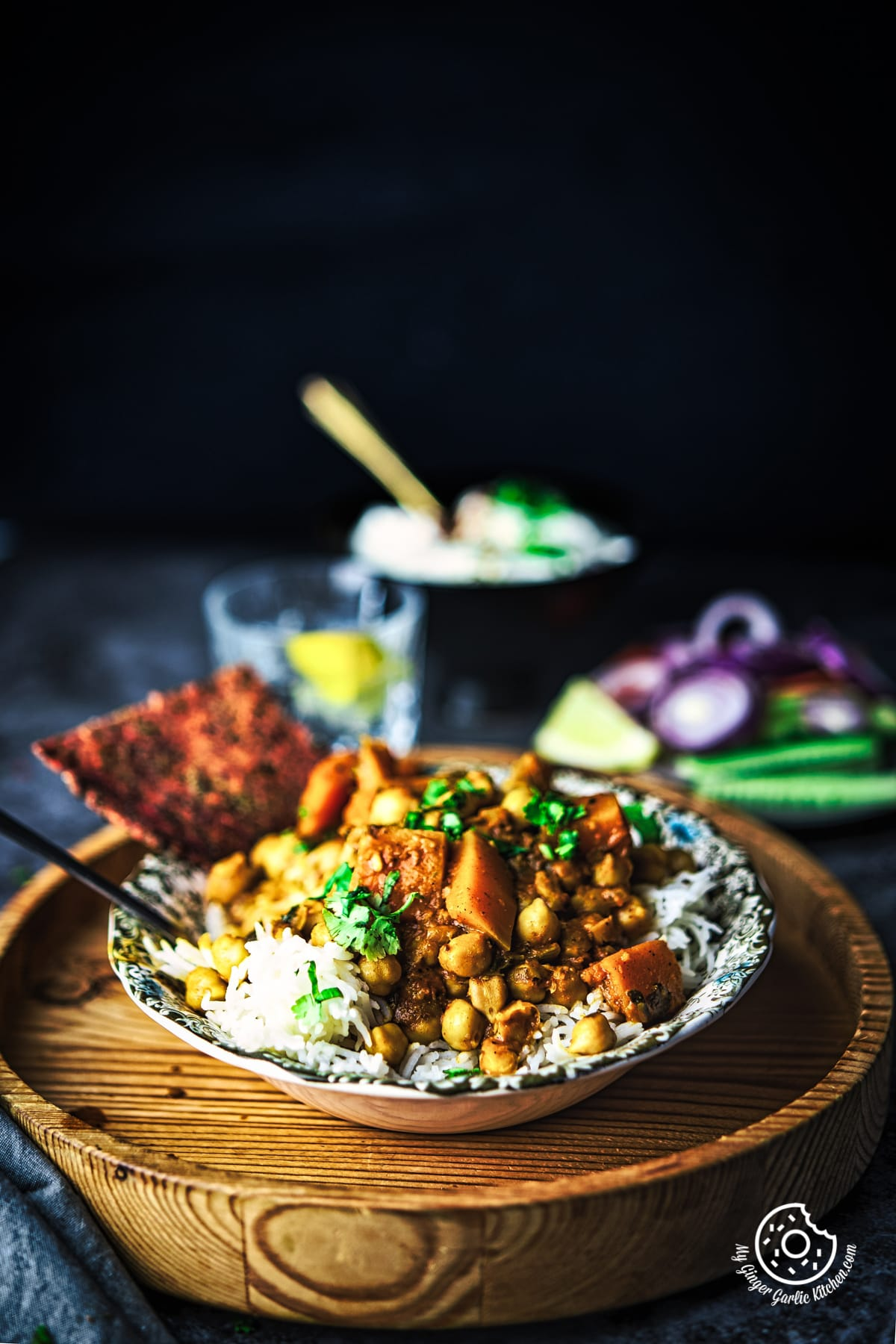image of butternut squash chickpea curry served in a white bowl over wooden board