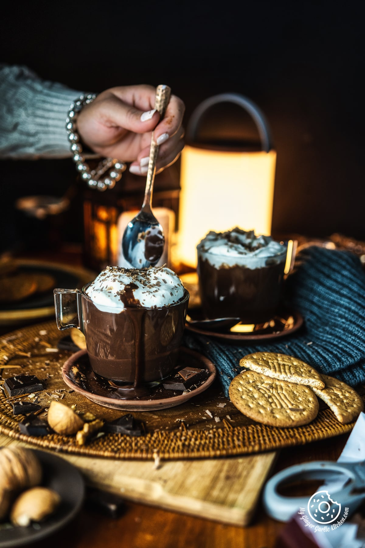 a women holing a spoon over Italian Hot Chocolate mug topped with whipped cream and chocolate shavings