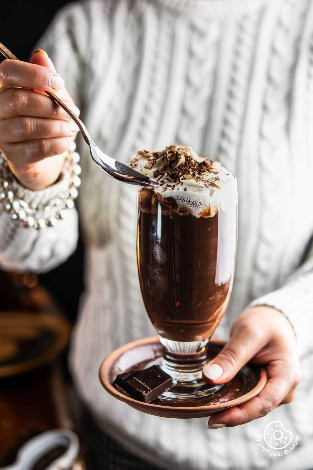 A female holding a transparent tall glass of Italian Hot Chocolate