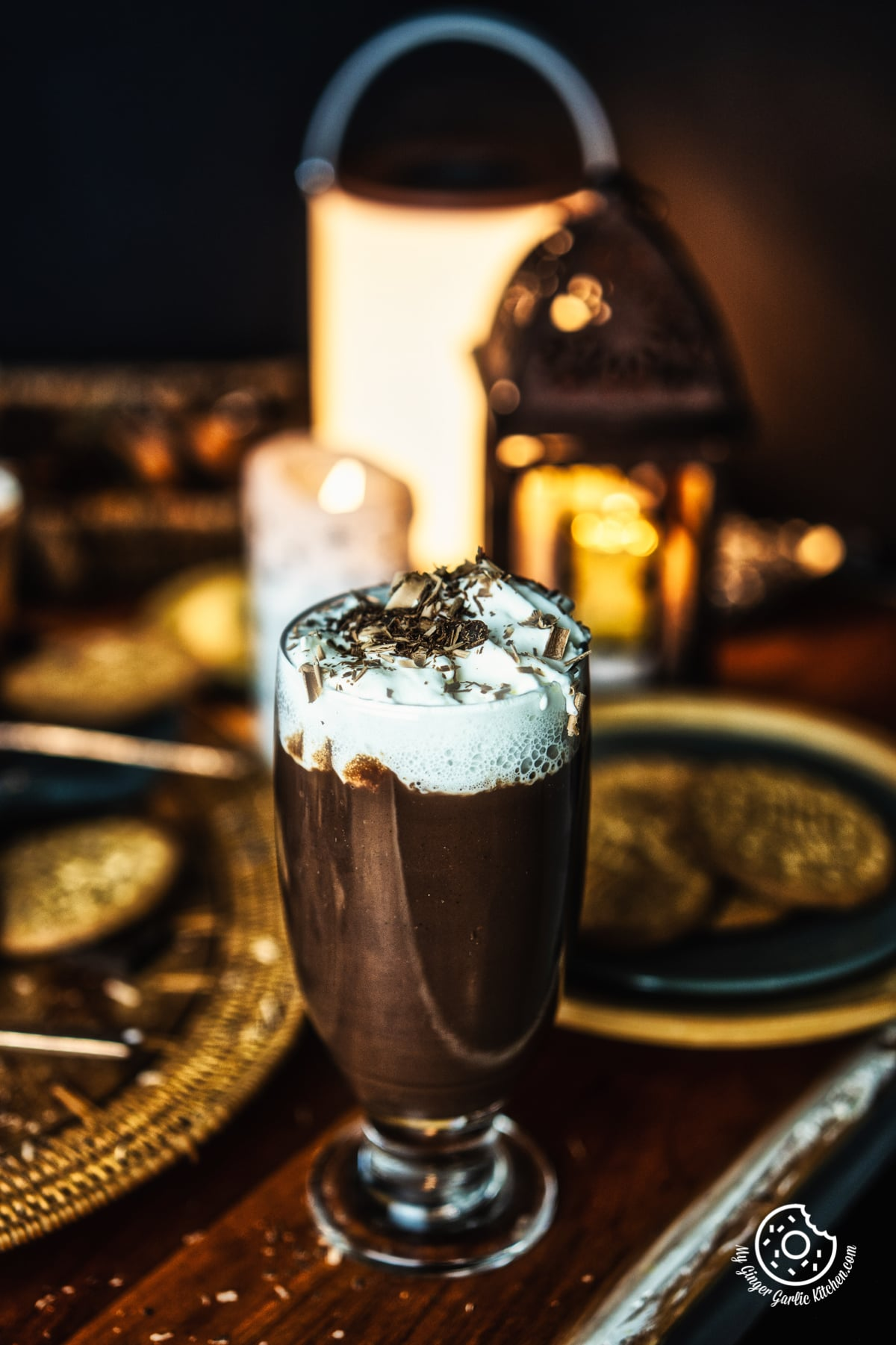 Italian Hot Chocolate with whipped cream and chocolate shavings in a transparent tall glass