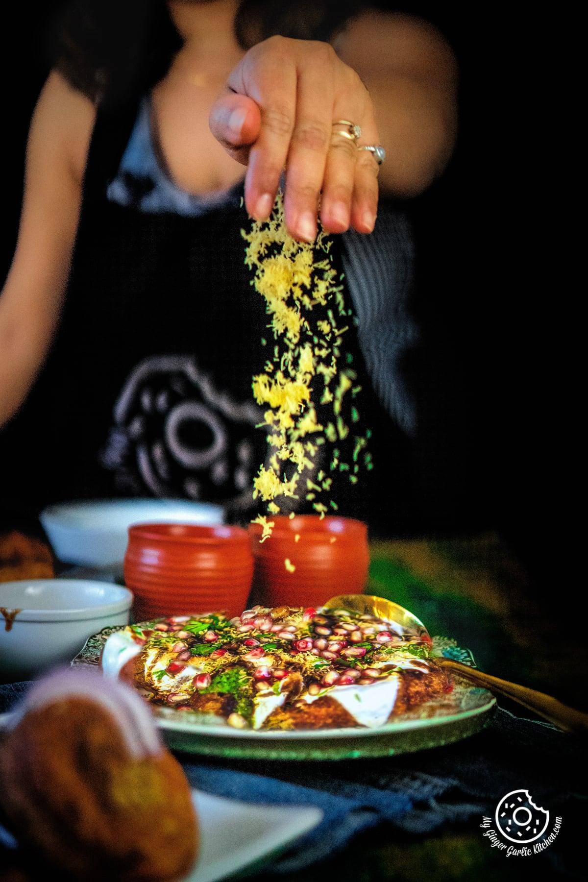 a female hand sprinkling sev on aloo tikki chaat platter