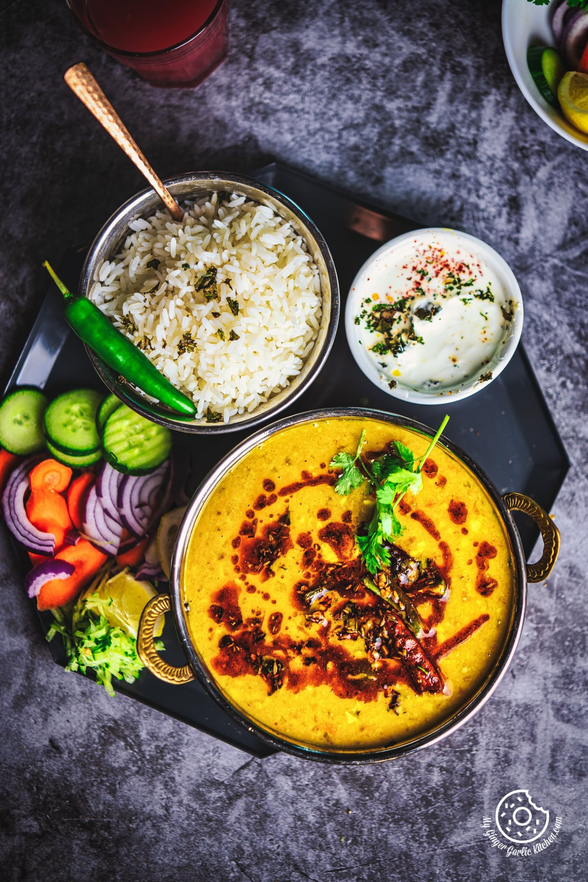overhead image of toor dal tadka served in a copper bowl