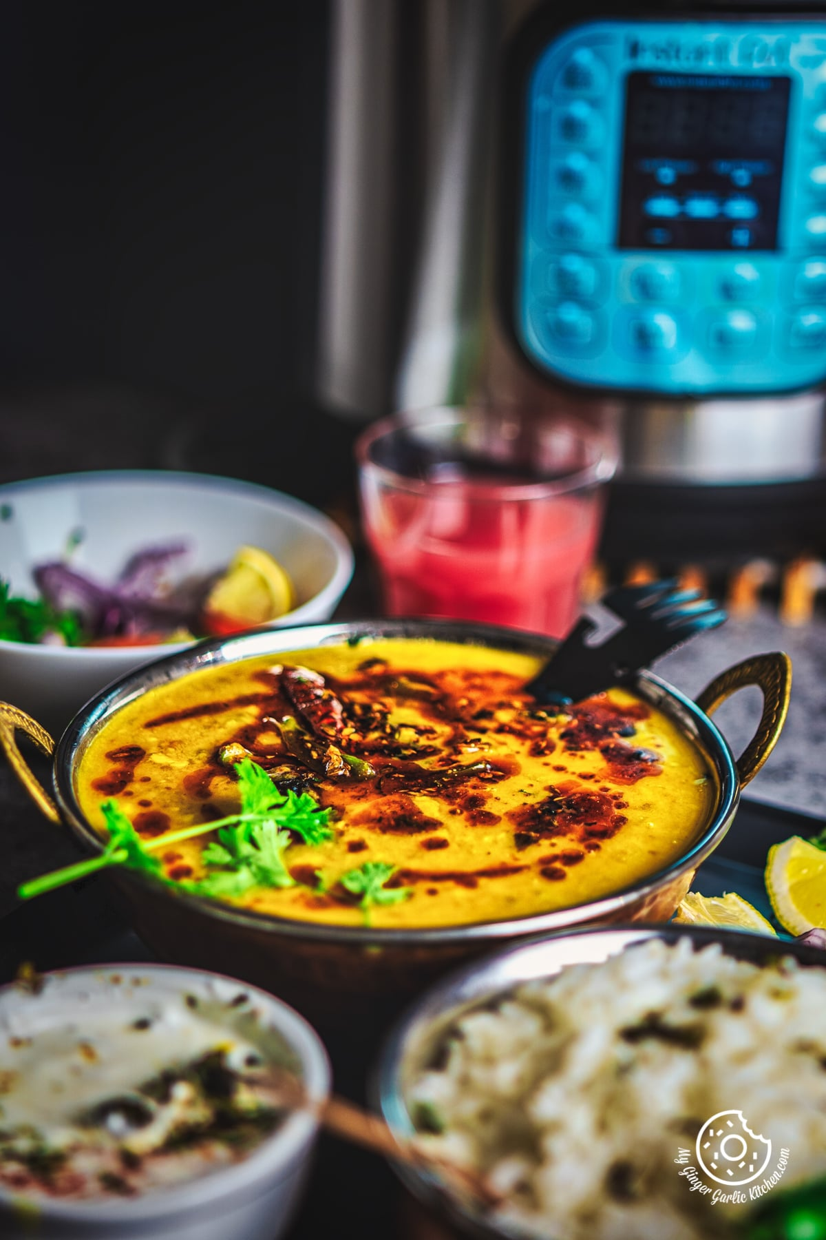Toor Dal Tadka in a metal bowl along with some white rice and instant pot in background