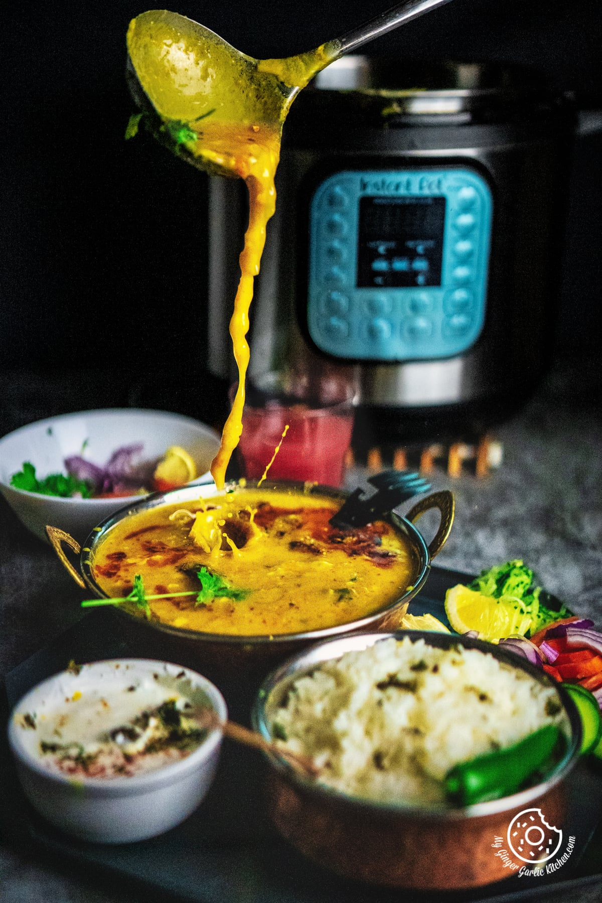 action shot of pouring Toor Dal Tadka from a ladle into a toor dal bowl