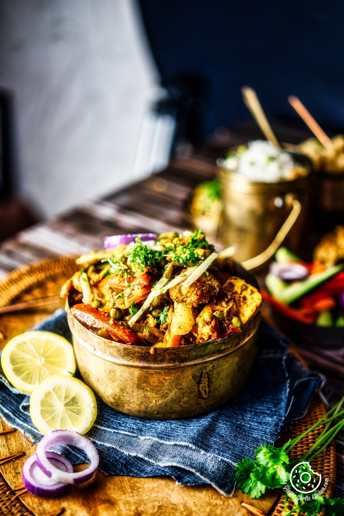 vegetable jalfrezi served in a brass bowl with lemon slices on the side