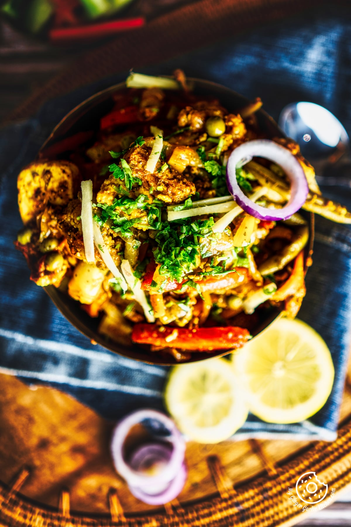 overhead closeup shot of vegetable jalfrezi served in a brass bowl