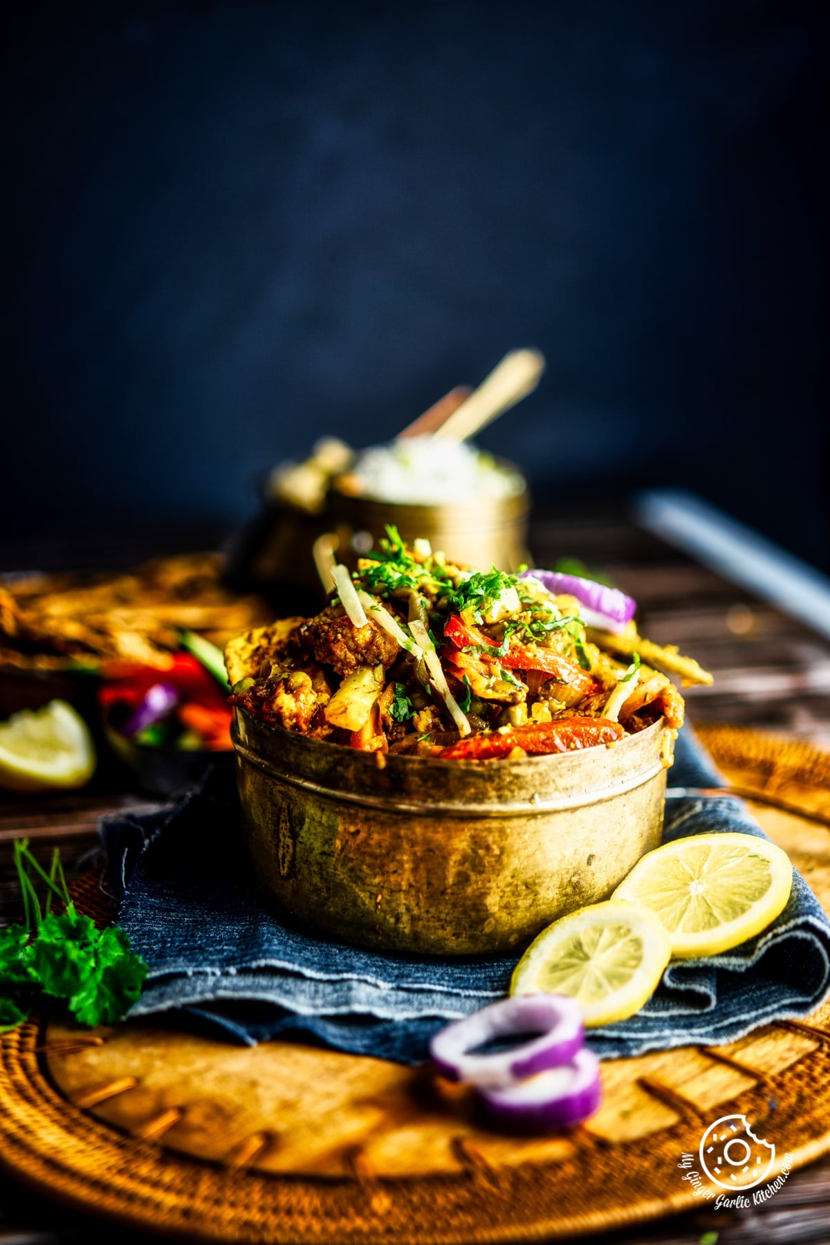 vegetable jalfrezi served in a brass bowl kept on a wooden board