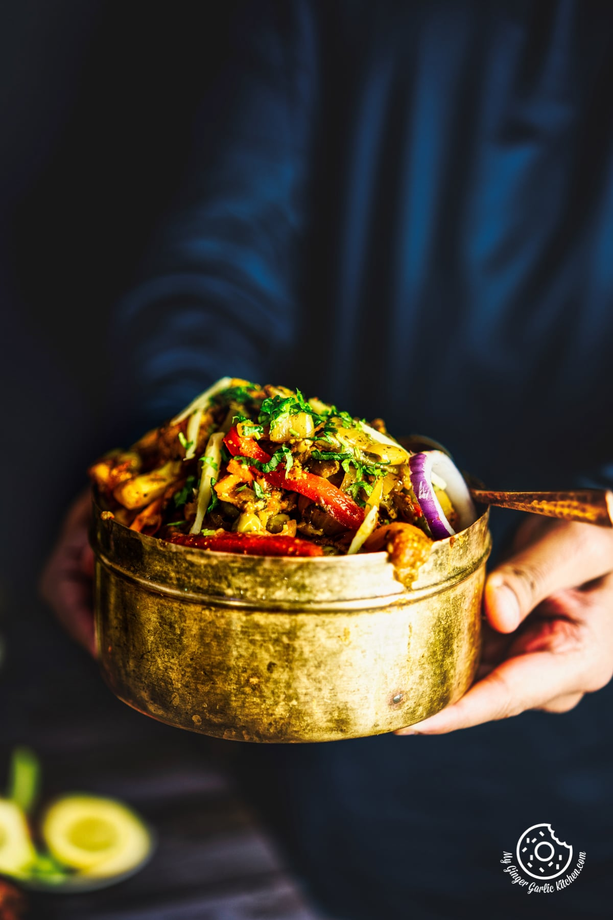 a person holding vegetable jalfrezi served in a brass bowl