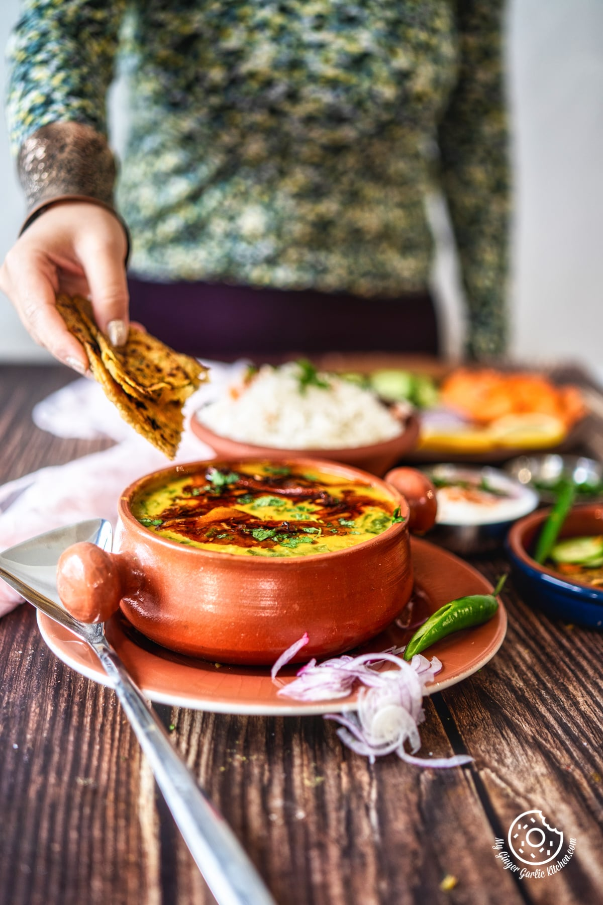 a female holding a piece of flatbread over dal palak bowl