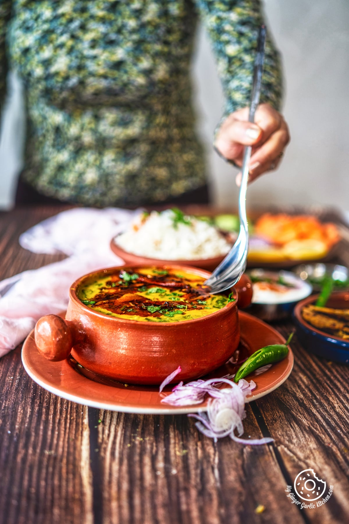 a female holding a steel spoon over dal palak bowl