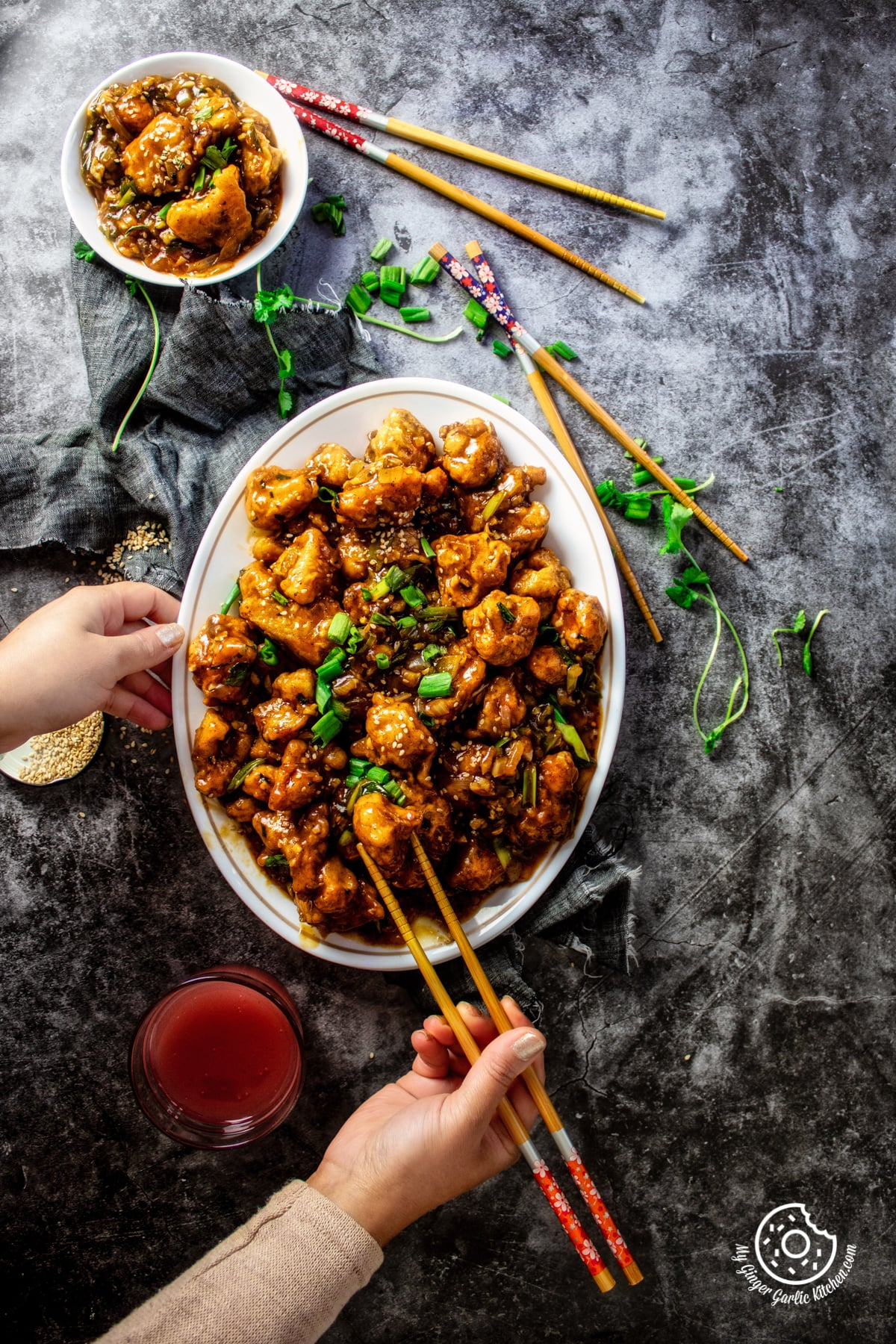 overhead shot of gobi manchurian a white oval plate where female hands holding wooden chopsticks