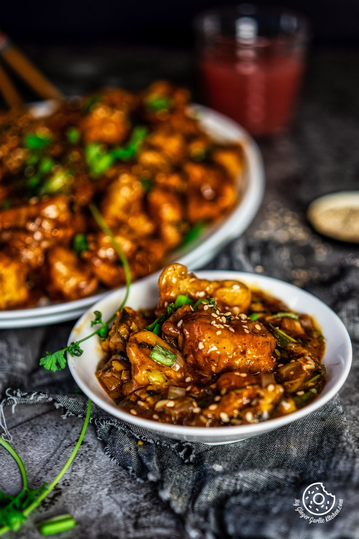 gobi manchurian topped with sesame seeds served in a white bowl