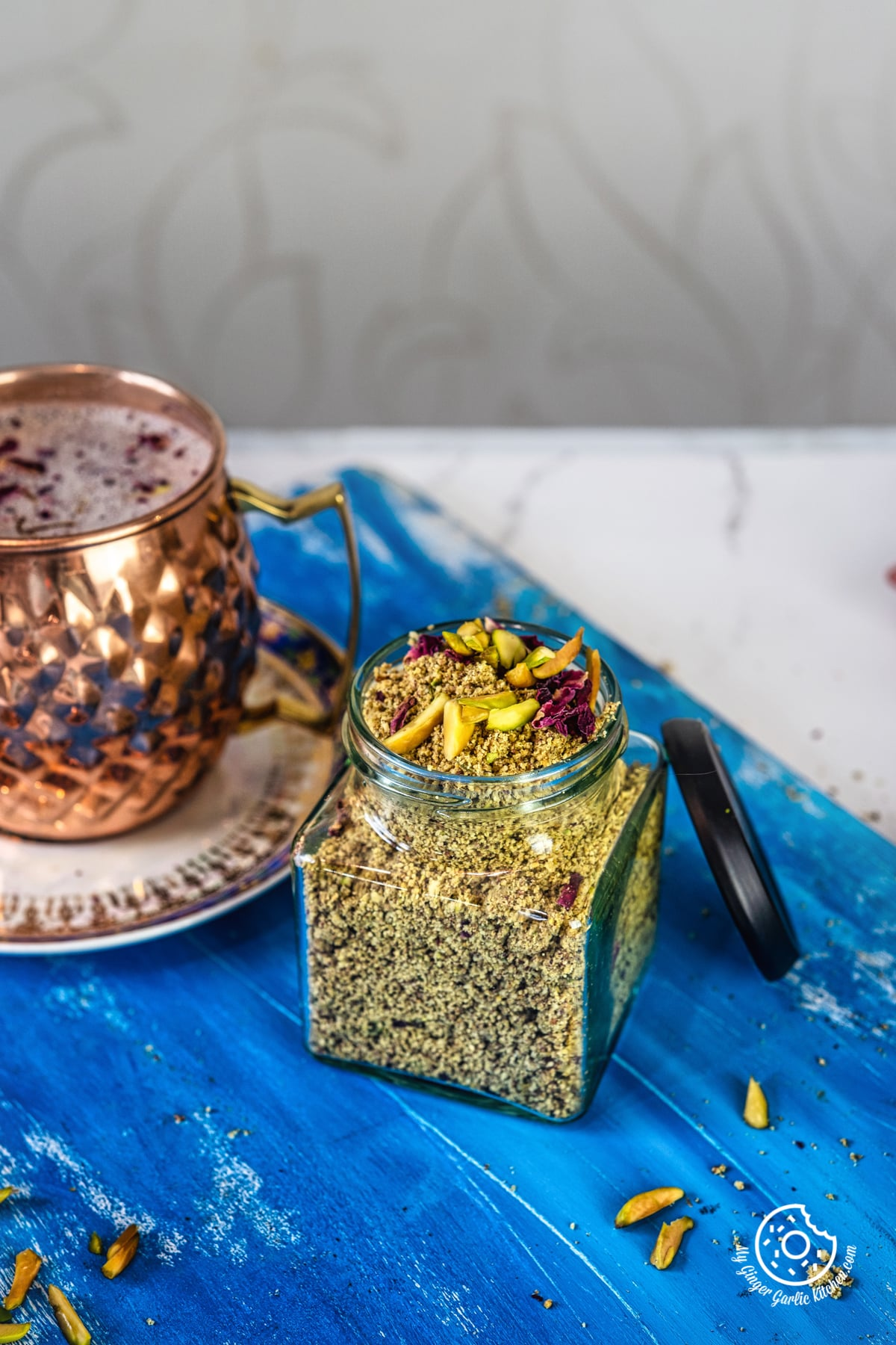 thandai powder in a transparent jar over blue wooden board and a copper mug on the side