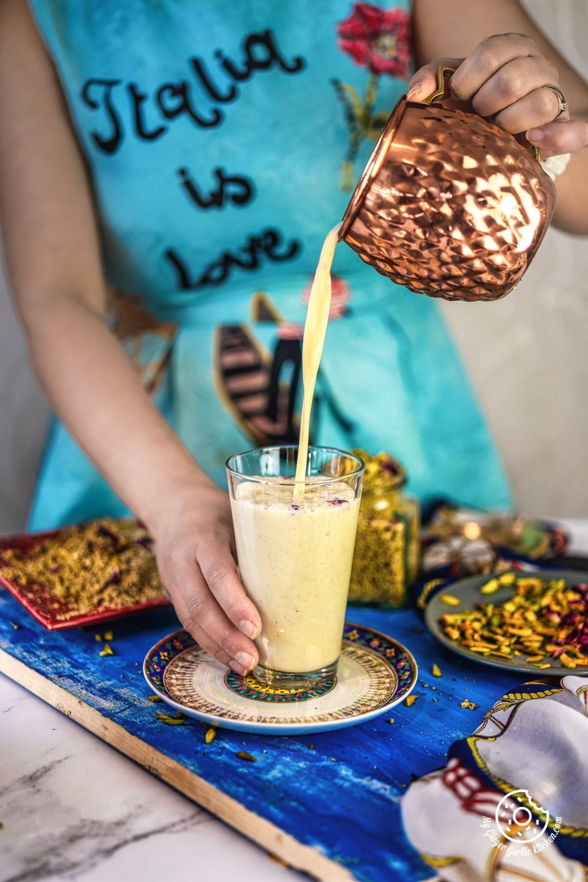a female pouring thandai in a transparent glass from a copper mug