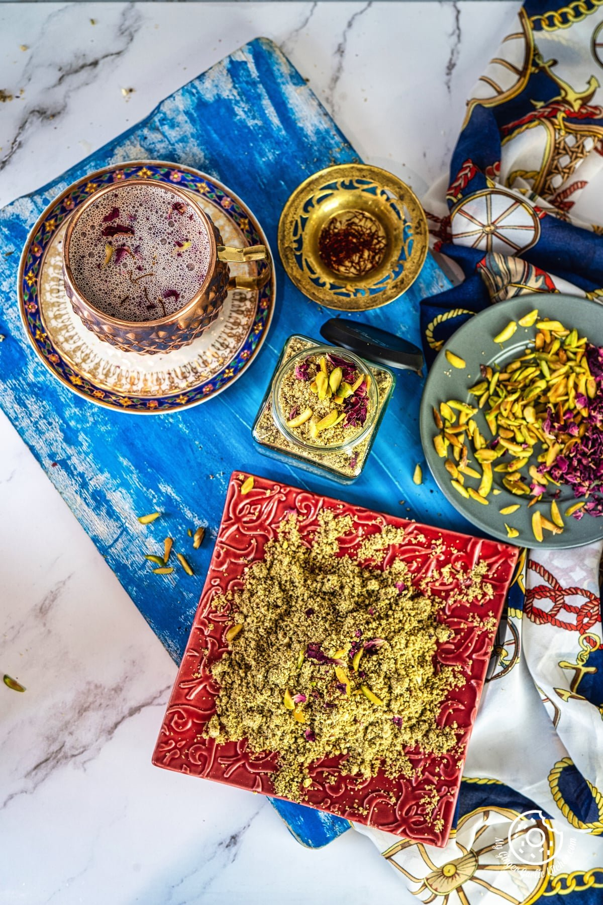 overhead shot of thandai powder in a red plate and in a transparent jar and thandai milkshake on the side