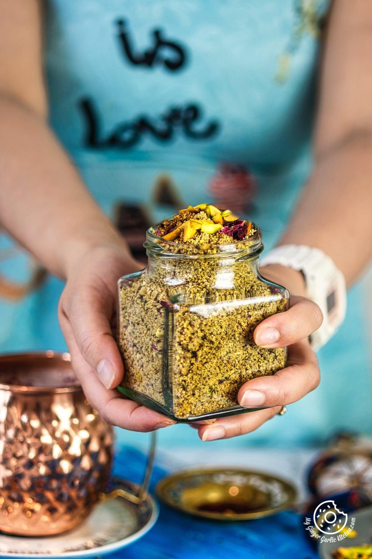 a female is holding a transparent thandai powder jar