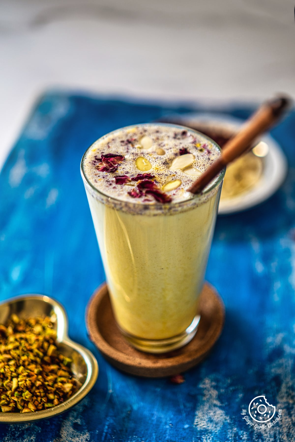 thandai milkshake topped with dried rose petals in a transparent glass kept on a wooden coaster