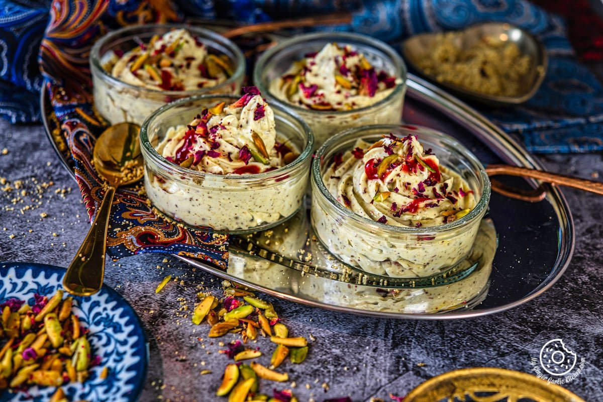 thandai shrikhand bowls topped with rose syrup, pistachios, and dried rose petals