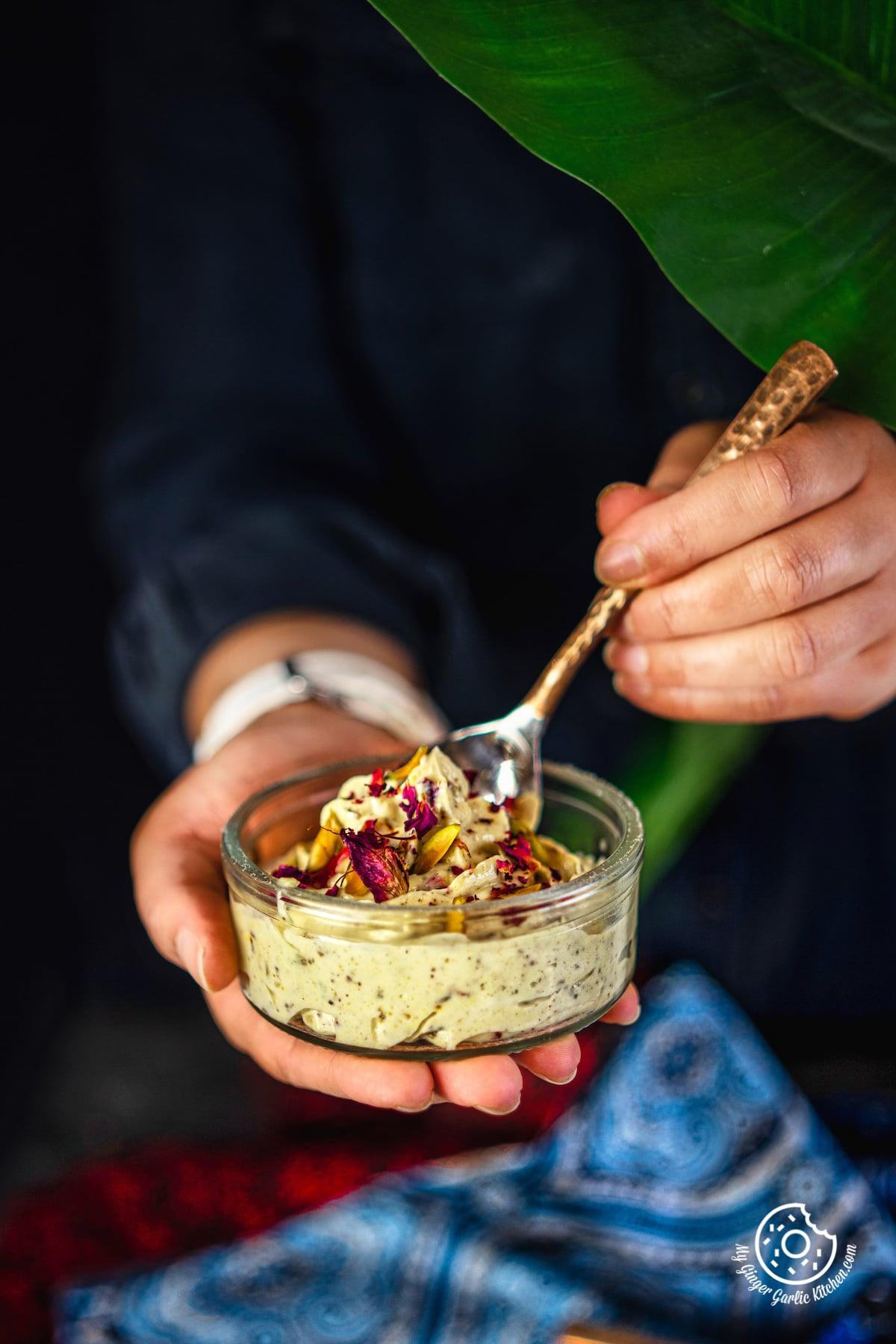 a female holding transparent bowl of thandai shrikhand