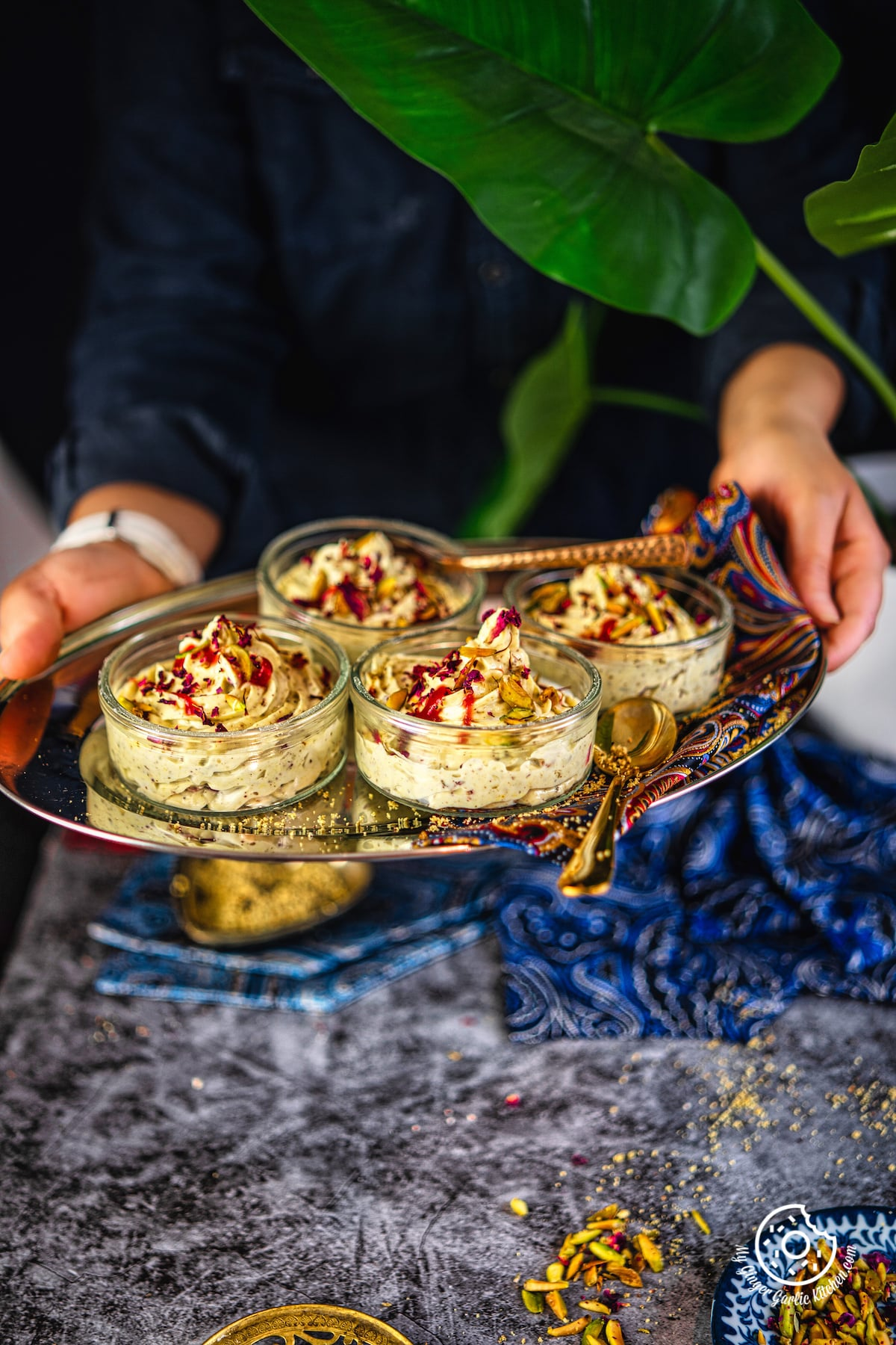 a female holding a metal tray with 4 transparent thandai shrikhand bowls