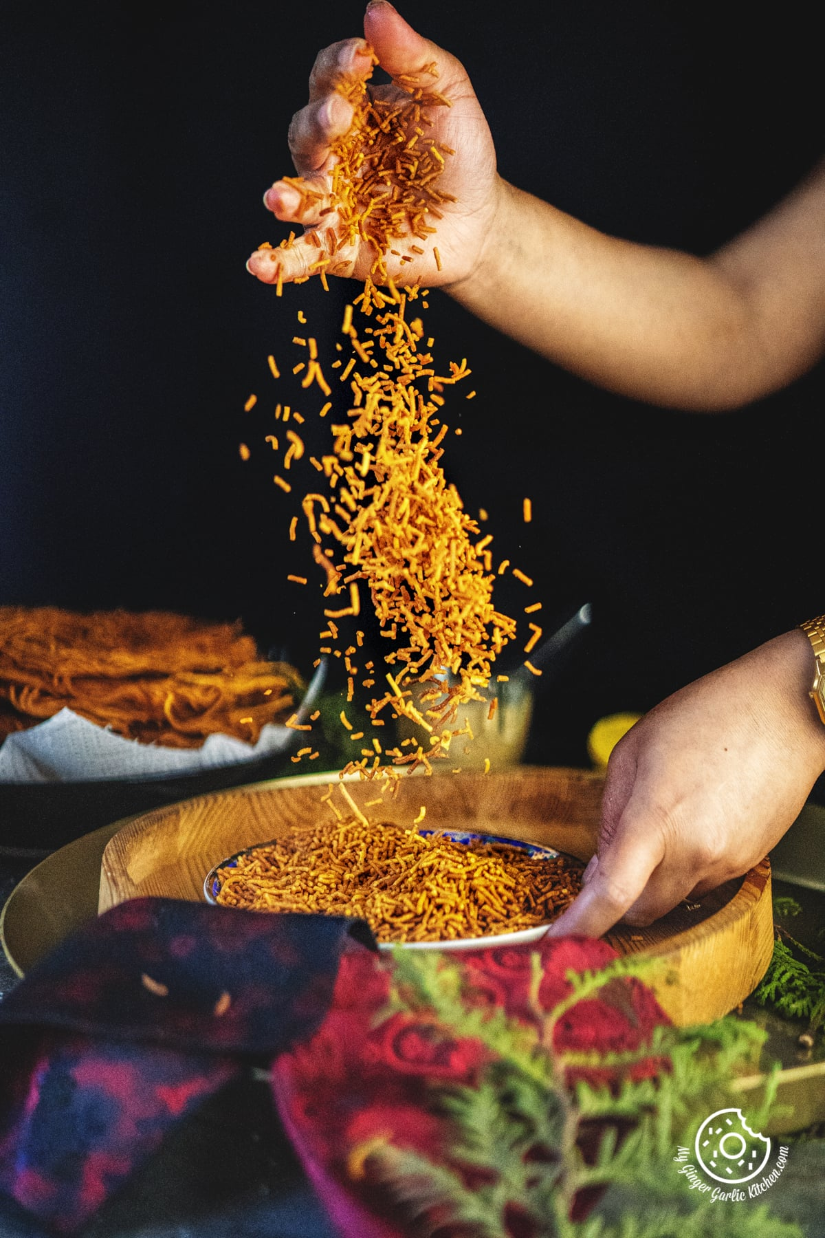 a female sprinkling aloo bhujia in a plate