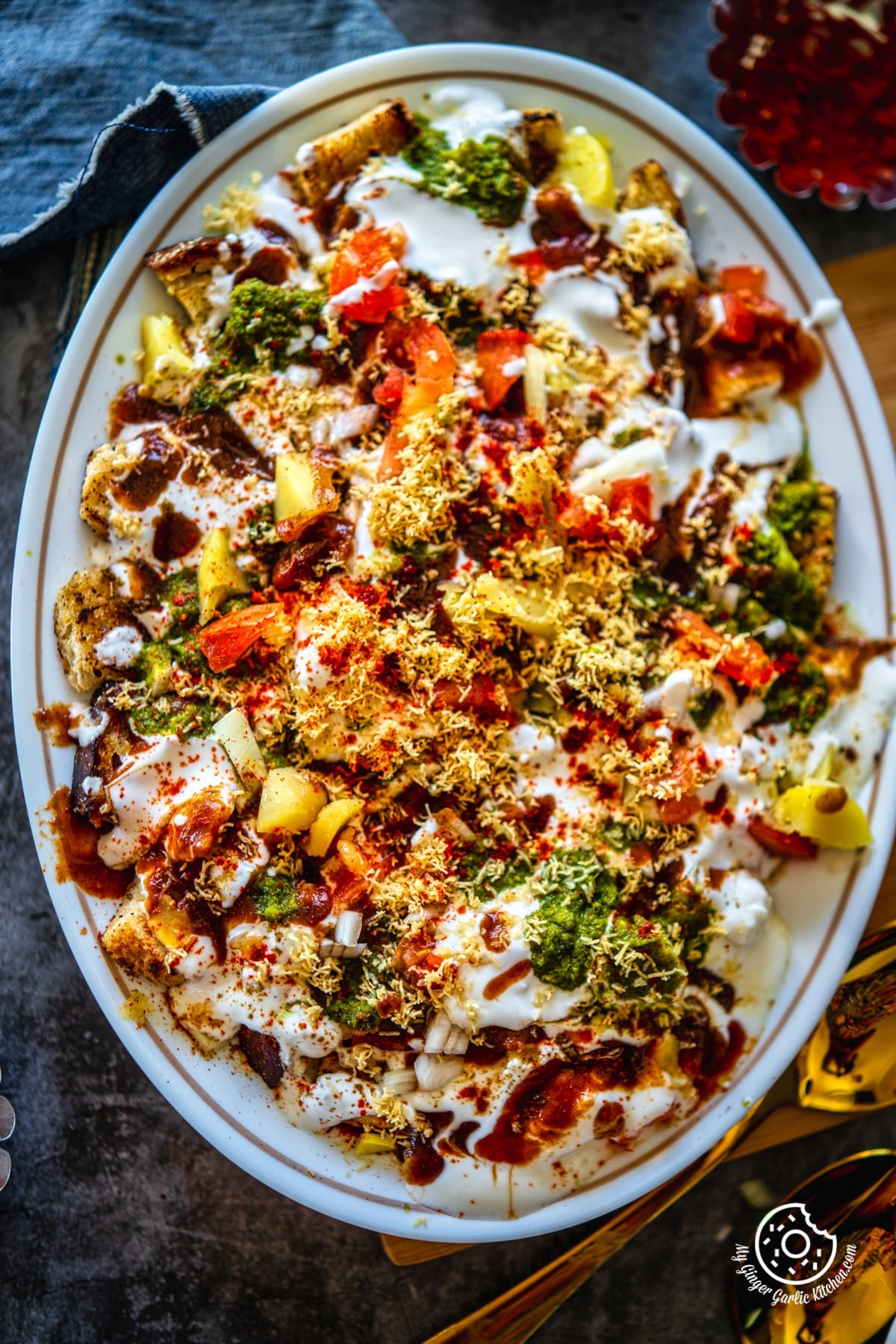 overhead closeup shot of bread dahi chaat served in a white oval shaped plate