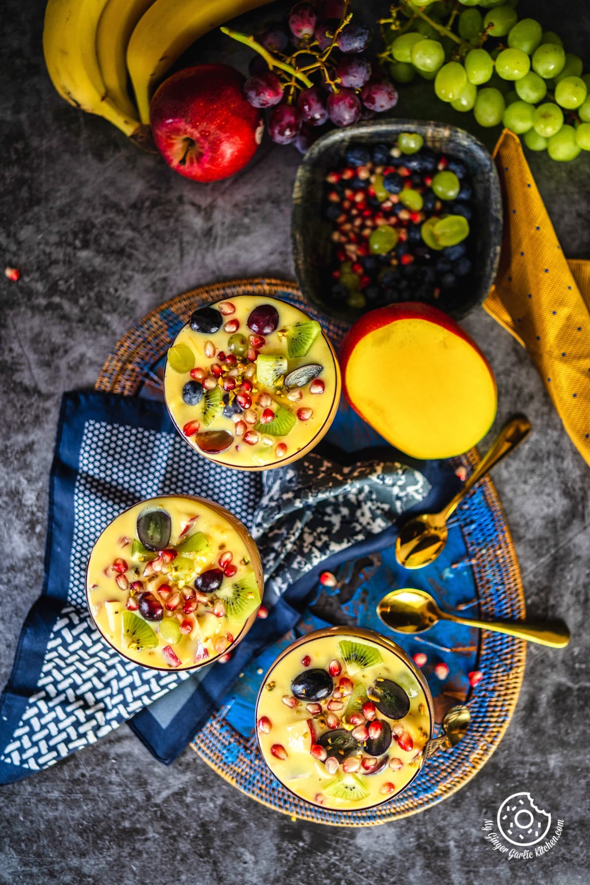 overhead shot of 3 fruit custard bowls with a half cut mango and other fruits