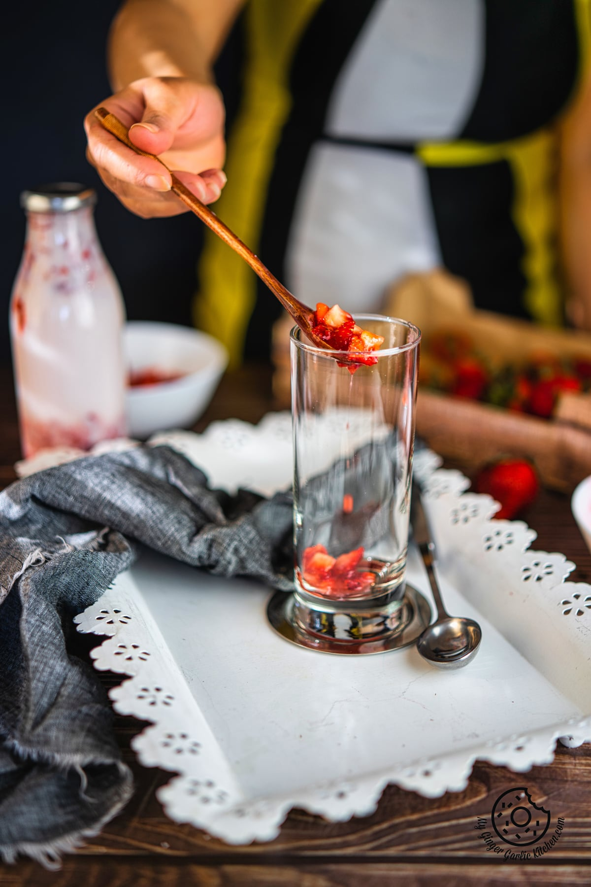 a hand hodling a wodden spoon with chopped strawberries over a tall glass