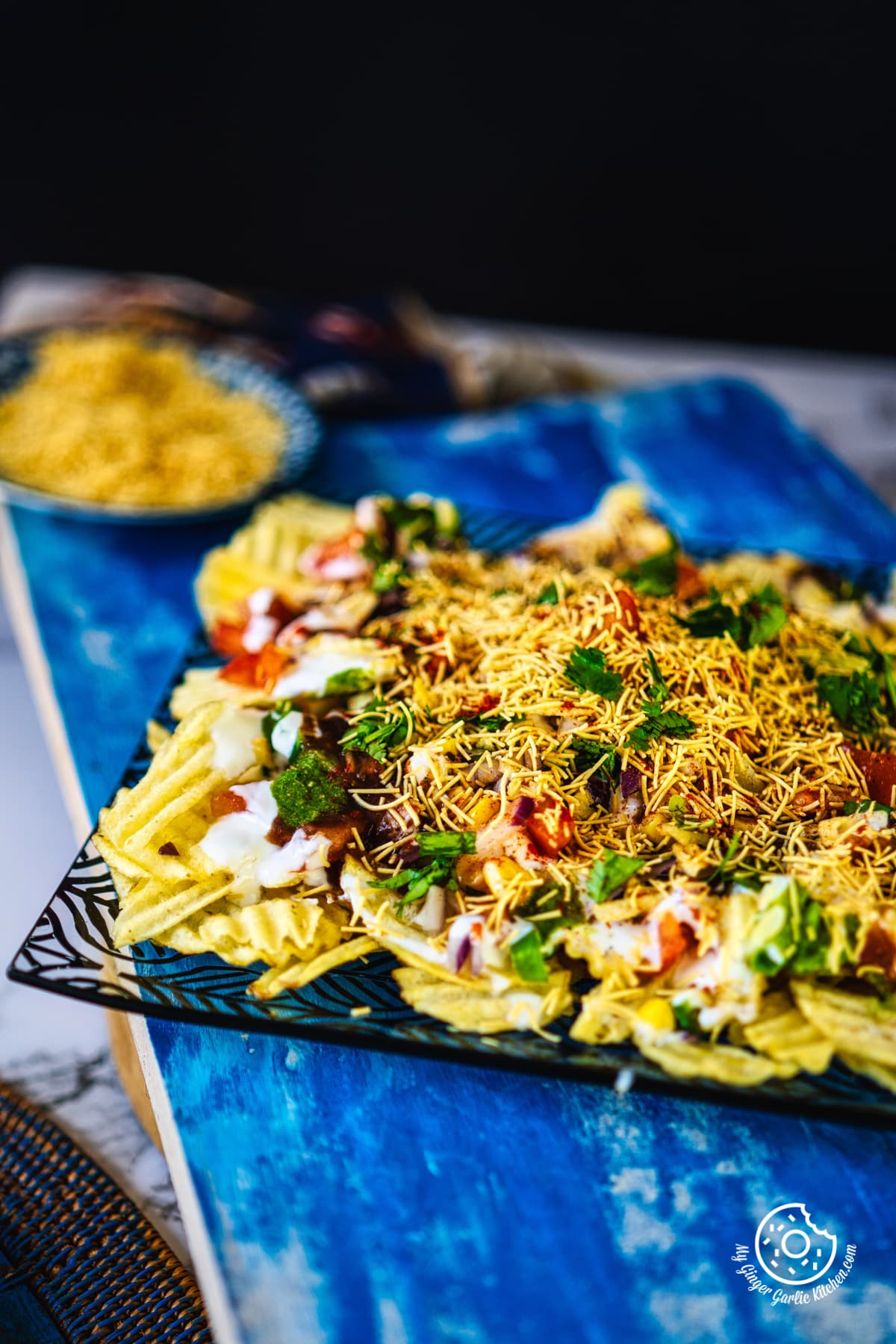 closeup shot of chips chaat served in a black and transparent plate