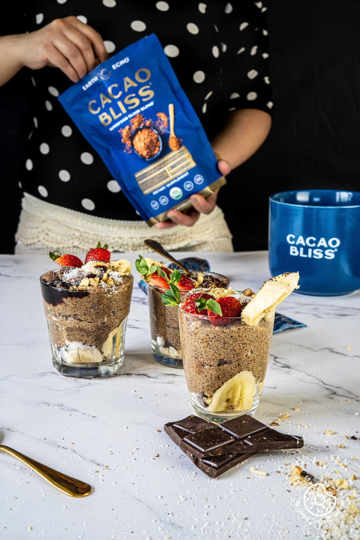three chocolate coffee chia pudding glasses kept on a white backdrop and a female holding a chocolate powder pouch in the background