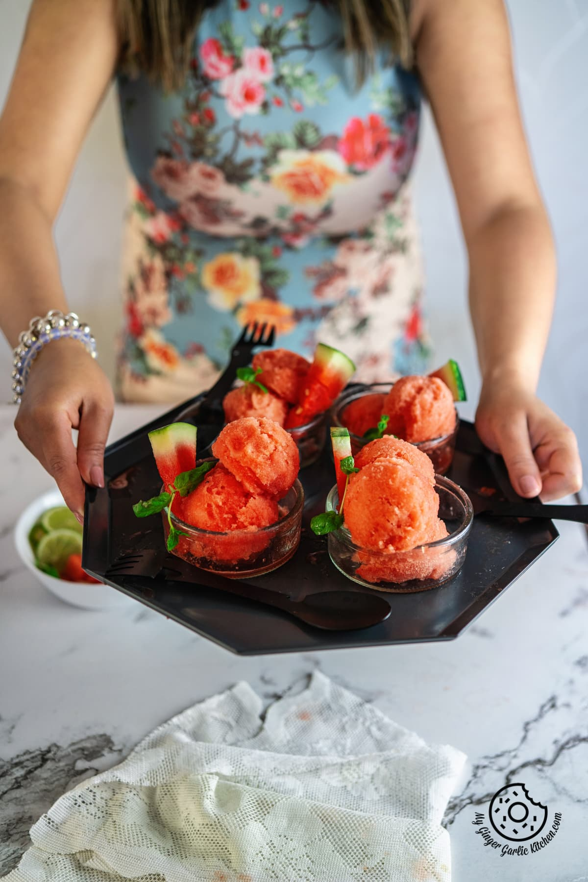 a female holding watermelon sorbet bowls tray